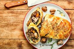 Tasty mushroom pie or wellington mushroom on old wooden table.English food