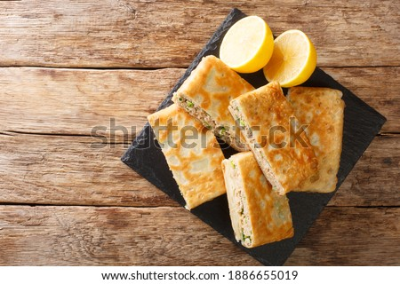 Tasty Mutabbaq Middle Eastern folded pan-fried flatbreads, stuffed with lightly spiced mince meat and egg closeup in the board on the table. horizontal top view above Foto d'archivio ©