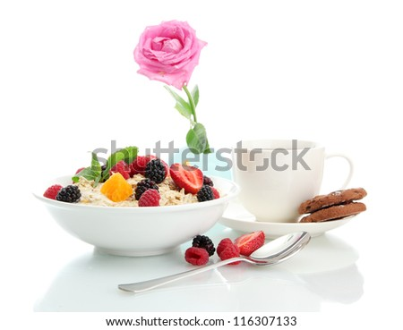 tasty oatmeal with berries and cup of tea, isolated on white