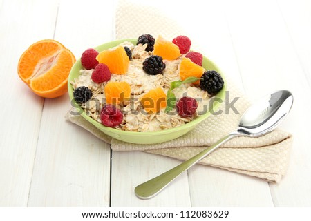 tasty oatmeal with berries and fruits, on white wooden table