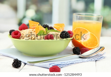 tasty oatmeal with berries and glass of juice on table, on window background