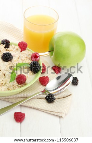 tasty oatmeal with berries and glass of juice, on white wooden table