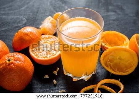 Tasty oranges and fresh glass of orange juice on the black wooden background. #797251918