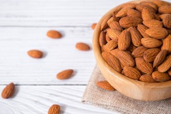 Tasty organic peeled almond snack in wooden bowl on white wooden background with copy space.Close up heap almonds shelled nut .Healthy food concept.