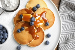 Tasty pancakes with blueberries served on wooden table, flat lay