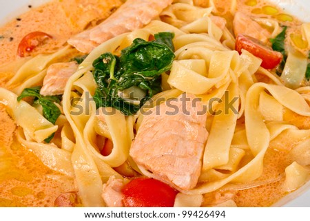 tasty pasta with cream, salmon, cheese and parsley close up