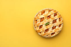 Tasty peach pie on color background
