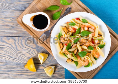tasty penne pasta salad with shrimps, mussels and baby spinach leaves on a white dish with vintage fork, caramelized balsamic vinegar in a sauce boat and lemon slices on an rustic table, top view