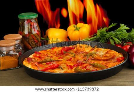 Tasty pepperoni pizza in pan with vegetables on flame background