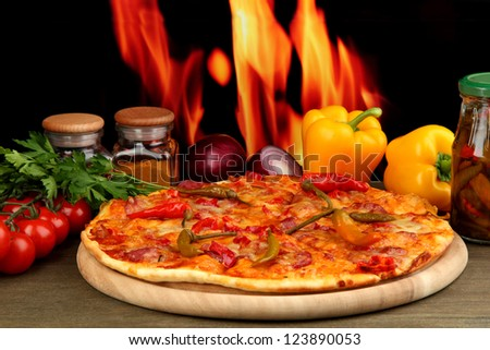 Tasty pepperoni pizza with vegetables on wooden board on flame background - stock photo