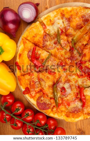Tasty pepperoni pizza with vegetables on wooden board on wooden background