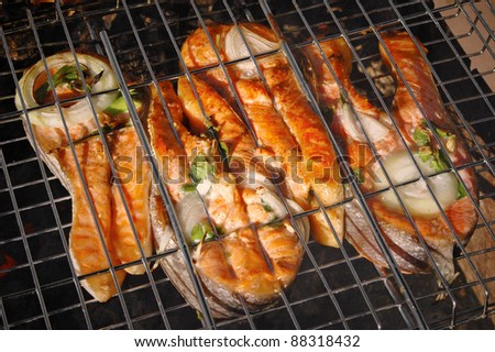 tasty pieces of salmon cooking on a grill