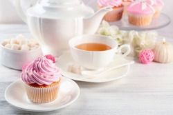 Tasty pink cupcake with cups of tea on light background