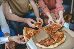 Tasty pizza. Male and female hands of three people holding pieces of pizza over box indoors, without face