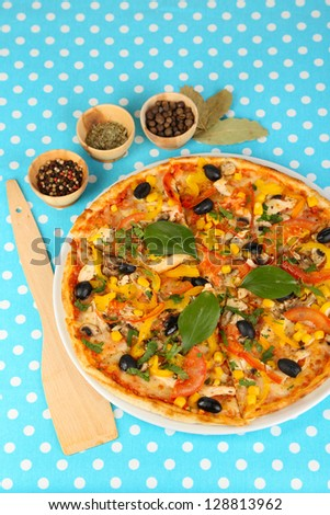 Tasty pizza on blue tablecloth close-up