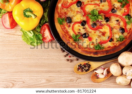 tasty pizza on the plate and vegetables on a wooden background