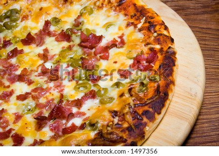 Tasty pizza on wooden plate and wooden table