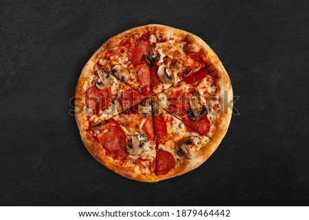 Tasty pizza with salame and mushrooms on dark concrete surface. Top view of sliced pizza.  Foto stock ©