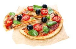 Tasty pizza with vegetables and basil on paper isolated on white