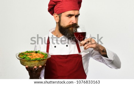 Tasty potato casserole dish served with fresh parsley and wine glass. Chef or man in burgundy cook uniform has supper in restaurant #1076833163