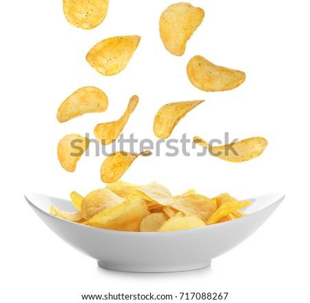 Tasty potato chips falling onto plate on white background