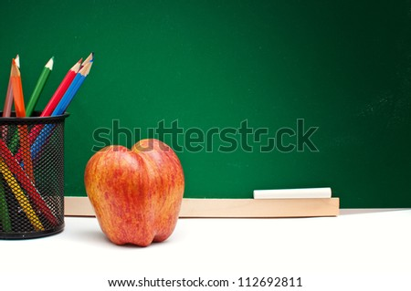 Tasty red apple and color pencils in front of the green chalkboard, back to school concept
