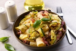 Tasty rigatoni pasta with courgette, prosciutto ham and grana padano cheese