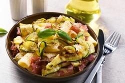 Tasty rigatoni pasta with courgette, prosciutto ham and grana padano cheese