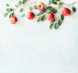 Tasty ripe red apples with branches and green leaves on rustic white background, top view. Border or frame with copy space for your design