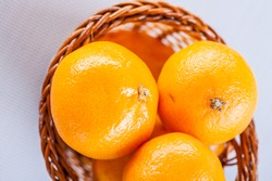 Tasty ripe tangerines lie in a wicker basket.
