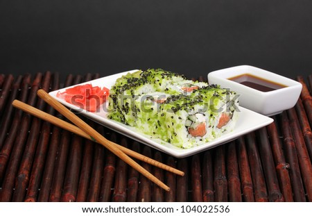 Tasty rolls served on white plate with chopsticks on bamboo mat on black background - stock photo