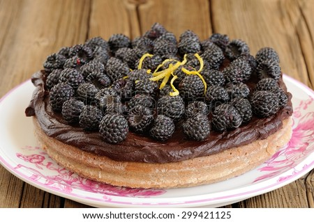 Tasty round homemade chocolate pie with ganache, decorated with fresh blackberries, lemon peel and icing sugar in white plate on wooden table