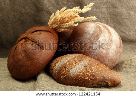 tasty rye breads with ears, on burlap background