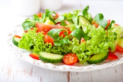 Tasty salad with different tomatoes, red pepper, lambs lettuce, cucumber, lettuce and lambs lettuce. Summer salad. Healthy snack. Concept for a tasty and healthy meal. White wooden background Close up