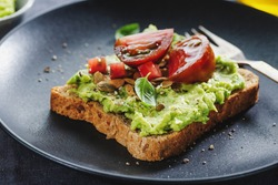 Tasty sandwich on wholegrain bread with mashed avocado and tomatoes. Closeup.