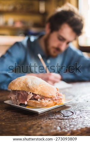 Tasty sandwich with ham and fresh bread with young man sitting at kitchen table and sketching