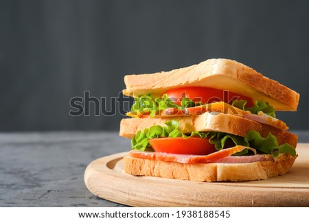 Tasty sandwich with ham, salad, cheese and tomatoes on gray background, selective focus, close-up view Foto stock ©