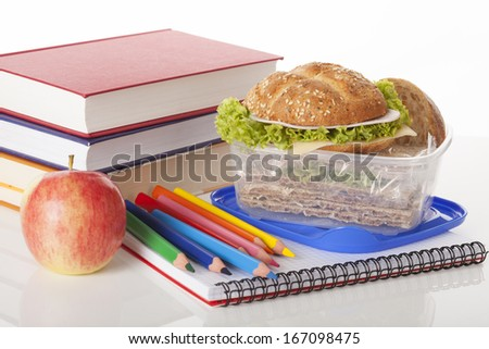 Tasty sandwiches with green lettuce in container and school supplies