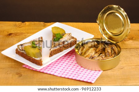Tasty sandwiches with sprats on plate on wooden table on brown background