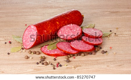 Tasty sausage and spices on wooden background