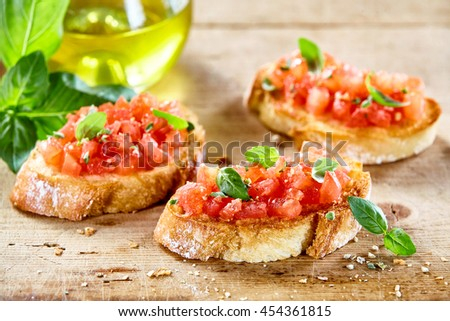 Tasty savory tomato Italian appetizers, or bruschetta, on slices of toasted baguette garnished with basil, close up on a wooden board