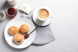 Tasty scones with clotted cream and jam on grey background, top view