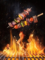Tasty skewers flying above cast iron grate with fire flames. Freeze motion barbecue concept.