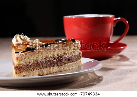 Tasty slice of layered coffee cake on a white plate, along with red coffee cup and saucer. Cake topped with syrup, chocolate sauce, whipped cream and flaked nuts.
