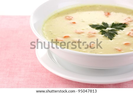 Tasty soup on pink tablecloth isolated on white