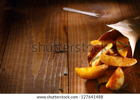 Tasty spicy potato wedges with fresh rosemary leaves spilling out of a rolled paper takeaway container onto textured wooden boards with copyspace