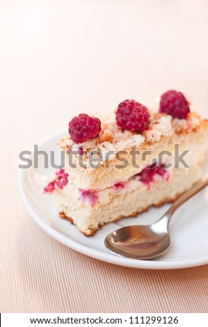 Tasty sponge cake with raspberries and curds as filling on a white plate with spoon on a textured table. Main focus on front raspberry and fore top part of the cake