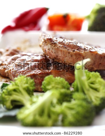 Tasty steak with vegetables against white background