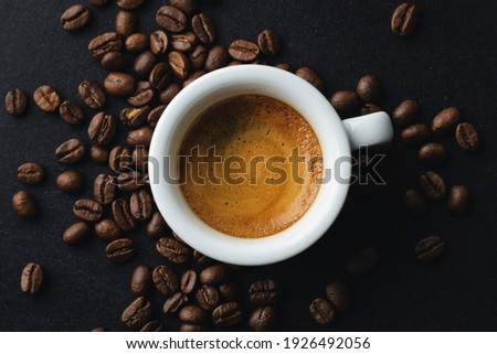 Tasty steaming espresso in cup with coffee beans. View from above. Dark background.  Stockfoto ©
