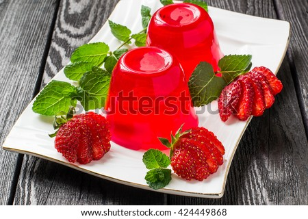 Tasty strawberry jelly and ripe strawberries on plate on a dark wooden table. Selective focus Stock photo ©